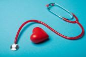 Dekoratives Herz neben rotem Stethoskop auf blauem Hintergrund, Konzept zum Weltgesundheitstag