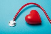Fotografie Dekorativní srdce a červený stetoskop na modrém pozadí, světový zdravotní den koncept