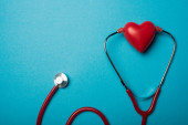 Top view of stethoscope connected with decorative red heart on blue background, world health day concept