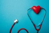 Top view sztetoszkóp kapcsolódik dekoratív piros szív kék háttér, világegészségügyi nap koncepció