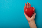 Fotografie Top view of woman holding decorative red heart on blue background, world health day concept