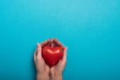 Top kilátás dekoratív piros szív nő kezében kék háttér, világegészségügyi nap koncepció
