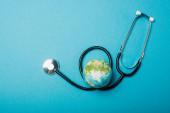 Top view of globe és sztetoszkóp kék háttér, világegészségügyi nap koncepció