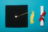 Photo Top view of black graduation cap with yellow tassel and diploma on blue background