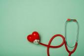 Horní pohled na stetoskop spojený s dekorativním červeným srdcem na zeleném pozadí, světový koncept dne zdraví