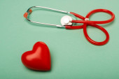 Stethoscope with decorative red heart on green background, world health day concept