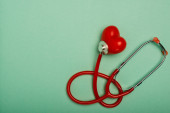 Top view of red stethoscope connected with decorative heart on green background, world health day concept