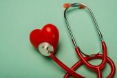 Fotografie Červený stetoskop spojený s dekorativním srdcem na zeleném pozadí, světový koncept dne zdraví