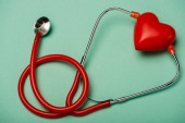 Red stethoscope and decorative heart on green background, world health day concept