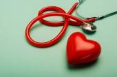 Stethoscope és piros szív zöld háttérrel, az egészség világnapja koncepció
