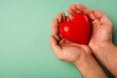 Vágott kilátás dekoratív piros szív az ember kezében zöld háttér, világegészségügyi nap koncepció