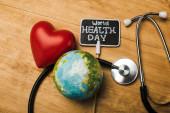 Fényképek Top kilátás dekoratív piros szív, sztetoszkóp, földgömb és kártya világegészségügyi nap felirat fa háttér