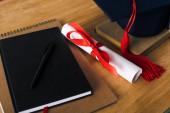 Notebooky, pero, diplom a maturitní čepice na dřevěném pozadí