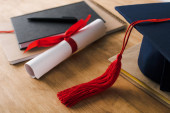 Selective focus of notebooks, pen, diploma and graduation cap with red tassel on wooden background