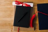 Horní pohled na notebooky, pero, diplom a červené střapce na dřevěném pozadí