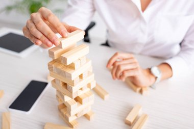 Selective focus of businesswoman playing blocks wood tower game at table stock vector