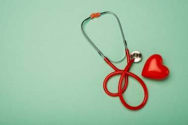 Top view of stethoscope next to red heart on green background, world health day concept stock vector