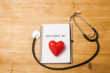 Top view of stethoscope, decorative heart on notebook with world health day lettering on wooden background stock vector