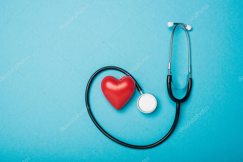 Top view of decorative heart and stethoscope on blue background, world health day concept stock vector