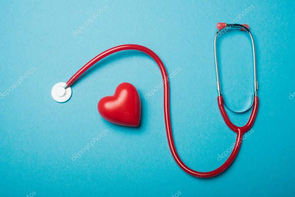 Top view of decorative heart next to red stethoscope on blue background, world health day concept stock vector