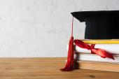 Diplom s krásnou mašlí, maturitní čepice s červeným střapcem na vrcholu knihy na stole na bílém pozadí