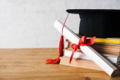 Photo Diploma with beautiful bow and graduation cap with red tassel on top of books on table on white background