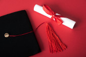 Photo Top view of diploma with beautiful bow and black graduation cap with tassel on red background