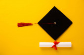 Photo Top view of diploma with beautiful bow and graduation cap with red tassel on yellow background