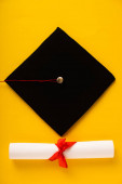 Photo Top view of diploma with beautiful bow and black graduation cap on yellow background