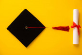 Photo Top view of diploma and graduation cap with red tassel on yellow background