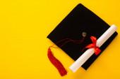 Horní pohled na černou maturitní čepici s červeným střapcem s diplomem nahoře na žlutém pozadí