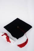Černá maturitní čepice s červeným střapcem a diplom na bílém pozadí