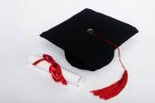 Černá maturitní čepice s červeným střapcem a diplom s lukem na bílém pozadí