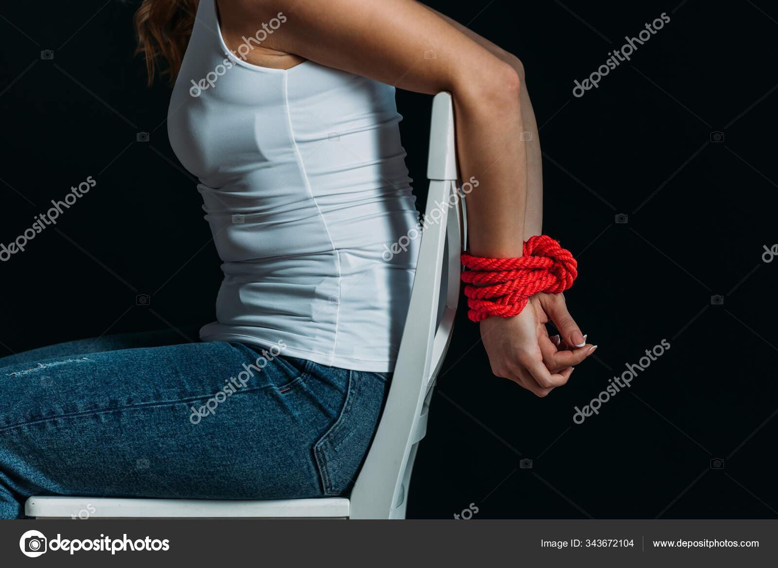elleri bagli beyaz sandalyede siyah uzerine izole edilmis kadin manzarasi 343672104