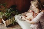 Žena fouká na ránu a sedí doma na pohovce