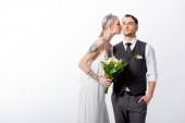 beautiful tattooed bride kissing handsome bridegroom isolated on white