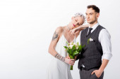 beautiful tattooed bride leaning on handsome bridegroom isolated on white