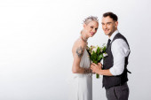 side view of smiling beautiful tattooed bride and handsome bridegroom holding hands isolated on white