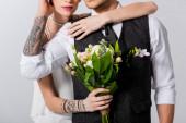 ostříhaný pohled na tetovanou nevěstu objímající ženicha izolované na šedé