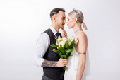beautiful tattooed bride and handsome bridegroom standing nose to nose isolated on white