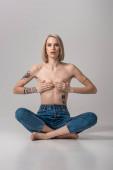 sexy junge tätowierte Frau oben ohne bedeckt Brust mit den Händen, während sie in Lotus-Pose auf grau sitzt