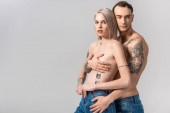 young shirtless tattooed couple in jeans hugging isolated on grey