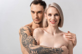 happy young naked tattooed couple hugging isolated on grey