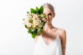 selektivní zaměření krásné tetované nevěsty a květinové kytice na bílém