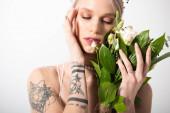 portré gyönyörű tetovált menyasszony pózol virágcsokor és csukott szemmel fehér