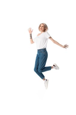 Full length view of happy blonde young tattooed girl jumping isolated on white stock vector