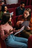 mladí multikulturní herci a herečky čtou scénáře na sedadlech v divadle
