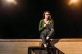 herečka vystupující se scénářem na jevišti v divadle