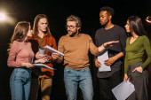 Photo multiethnic actors and actresses rehearsing with theater director on stage