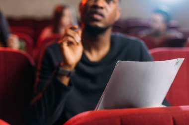 selective focus of multicultural young actor and actresses reading scripts in theater